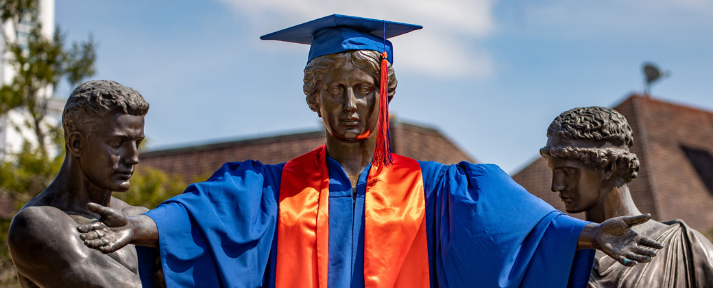 Alma Mater wearing a cap and gown with the tassel on the left